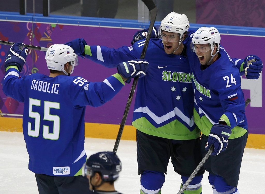Slovenia's Ticar celebrates his goal against Slovakia with teammates Kopitar and Sabolic during the third period of their men's preliminary round ice hockey game at the 2014 Sochi Winter Olympic Games